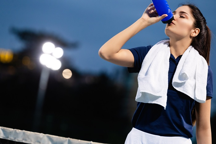 woman drinking after training