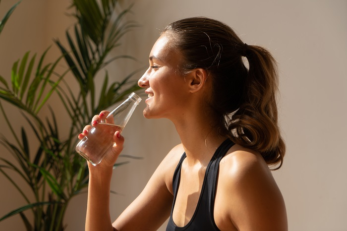 woman drinking filtered water at home